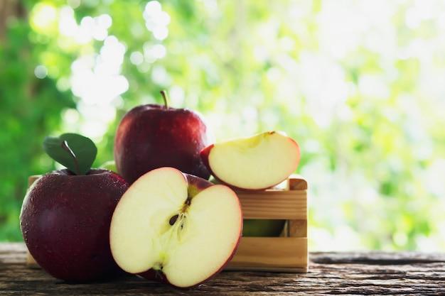 Maçã fresca em caixa de madeira sobre a natureza verde, frutas frescas