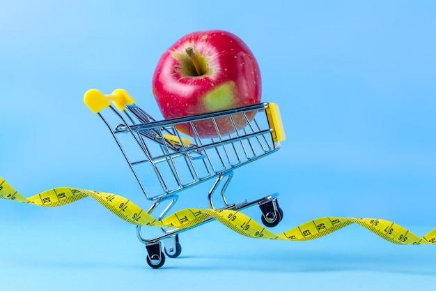 Maçã fresca em um carrinho de compras e fita métrica. conceito de dieta. planeje ficar em forma, praticar esportes e perder quilos extras