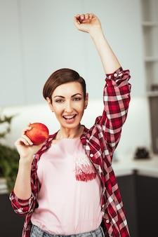 Maçã fresca em uma mão de dona de casa vestindo uma camisa xadrez com um penteado curto enquanto cozinha maçã