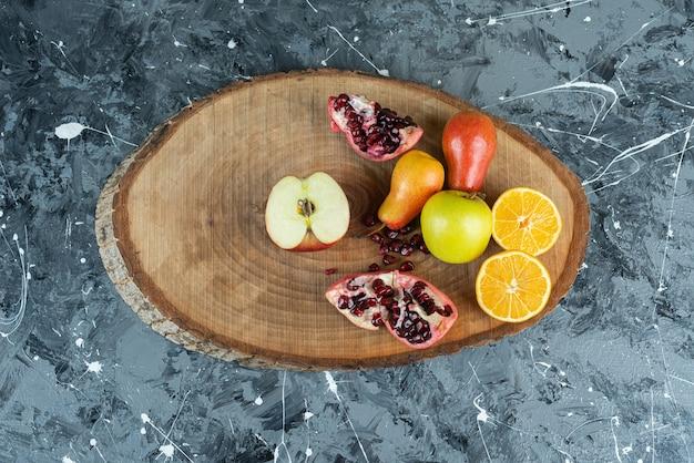 Maçã fresca, laranja, peras e romã na peça de madeira.