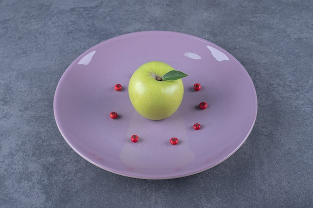 Maçã fresca orgânica verde na placa roxa.
