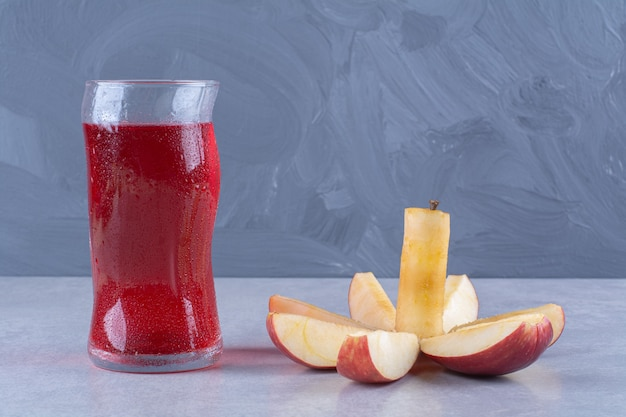 Maçã inteira e fatia ao lado de um copo de suco de cereja, sobre a mesa de mármore.