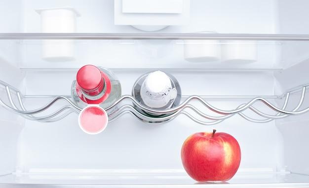 Maçã, iogurte e duas garrafas na geladeira