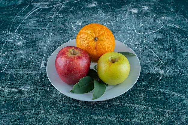 Maçã, laranja e folhas em um prato, na mesa de mármore.