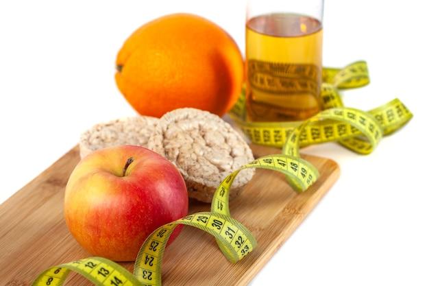Maçã, laranja, kiwi com fita métrica em fundo branco, dieta saudável.