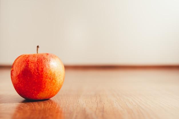 Maçã madura isolada no fundo branco e no assoalho de madeira, conceito da dieta para perder o peso no verão.
