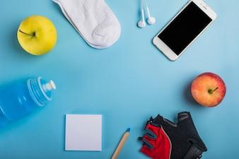 Maçã; meia; fone de ouvido; garrafa de agua; nota adesiva; lápis; luva e celular em fundo azul