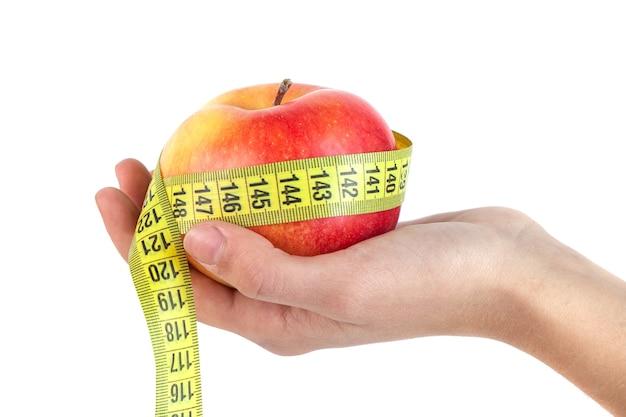 Maçã na mão com uma fita métrica em fundo branco, comida saudável