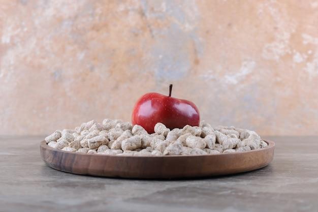Maçã nas migalhas de pão na tigela ao lado da espiga, na superfície de mármore