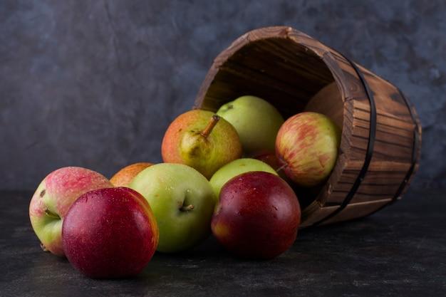 Maçã, pêssego e peras em um balde de madeira
