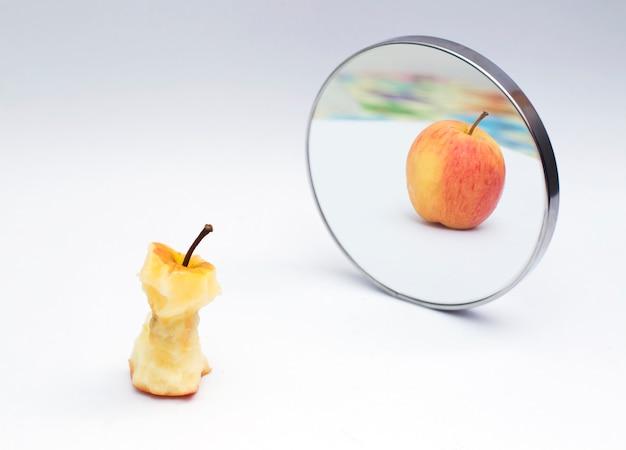 Maçã refletindo no espelho em fundo branco isolado
