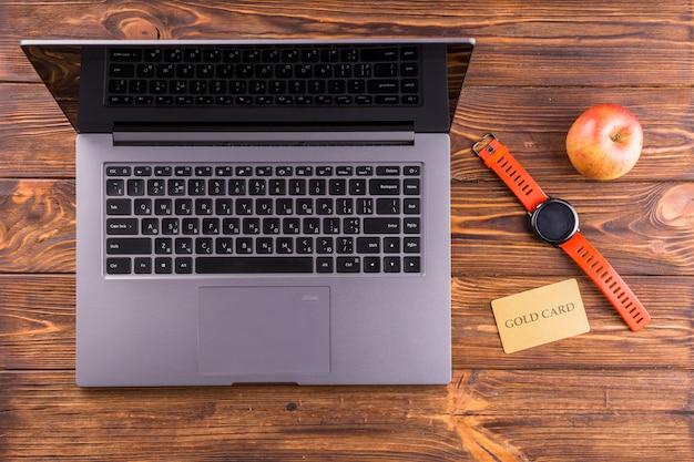 Maçã; relógio de pulso; laptop e cartão de ouro na mesa de madeira