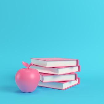 Maçã rosa e pilha de livros sobre fundo azul brilhante