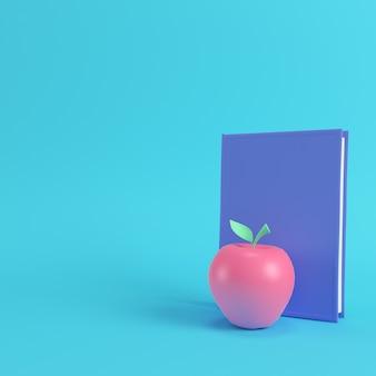 Maçã rosa em um livro sobre fundo azul brilhante