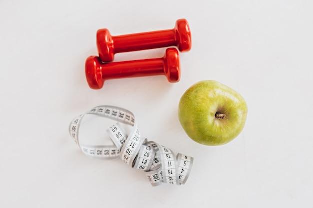 Maçã verde, centímetros e halteres vermelhos. conceito de saúde, dieta e esporte