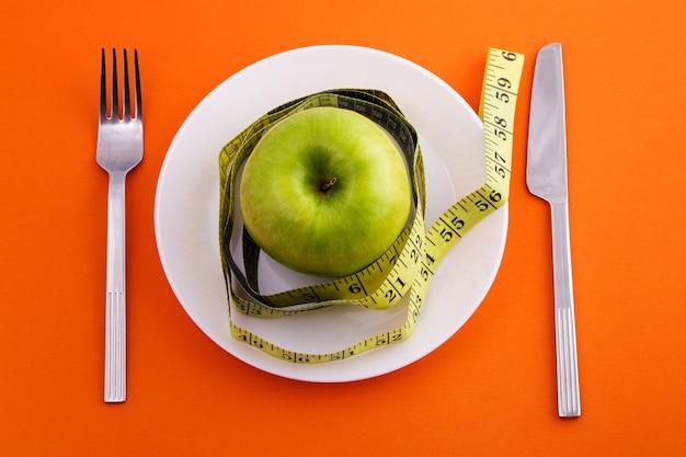 Maçã verde deitada em um prato branco com uma fita métrica rebobinada, faca e garfo em uma superfície laranja