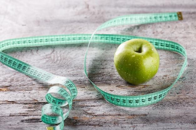 Maçã verde e centimetro. conceito de dieta alimentar ou saudável