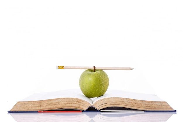 Maçã verde e lápis no livro.