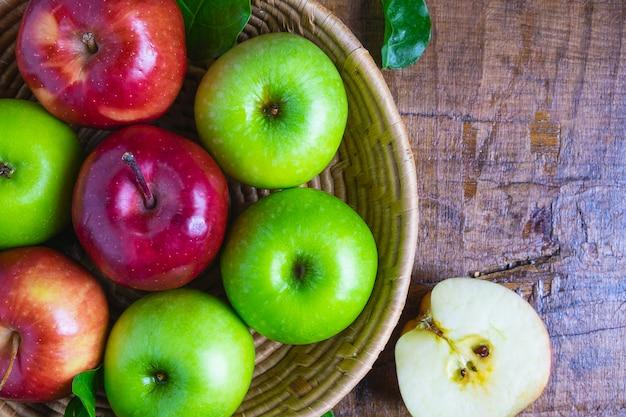 Maçã verde e maçã vermelha em uma cesta em um fundo de madeira