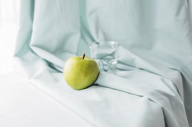 Maçã verde e um copo de água em uma toalha azul. conceito de cuidados de saúde e dieta