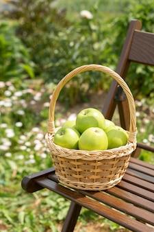 Maçã verde, em, cesta vime, ligado, cadeira jardim, grama verde, tempo colheita