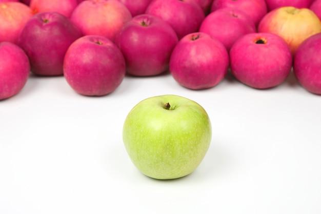 Maçã verde em um fundo de maçãs vermelhas em fundo branco. vitamina e comida saudavel