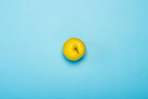 Maçã verde em uma superfície azul. minimalismo. conceito de trópicos, alimentação saudável, vitaminas. vista plana leiga, superior.