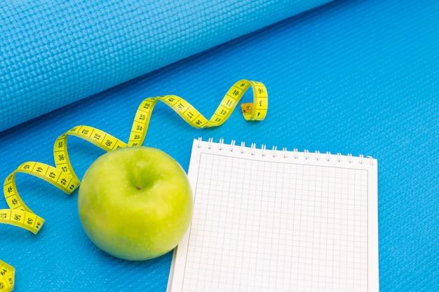 Maçã verde, fita métrica, caderno em uma esteira de esportes de fundo de cor azul. preparação para a temporada de verão e praia, perda de peso e conceito esportivo