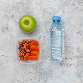 Maçã verde fresca, fita métrica e garrafa de água fresca em concreto cinza