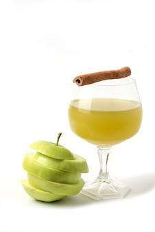 Maçã verde inteira e fatiada em branco com um copo de suco