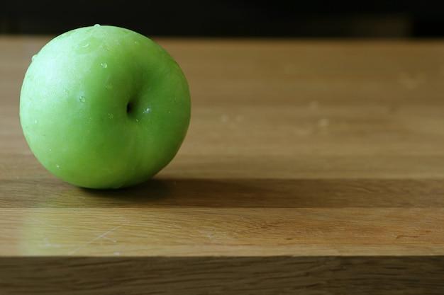 Maçã verde isolada em mesa de carvalho