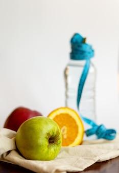 Maçã verde, laranja e água engarrafada com fita azul de medição sobre fundo branco, conceito de estilo de vida saudável.