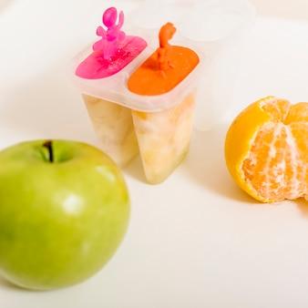 Maçã verde; laranja e picolé mofo na mesa