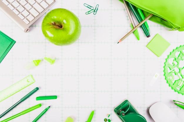 Maçã verde na mesa com artigos de papelaria