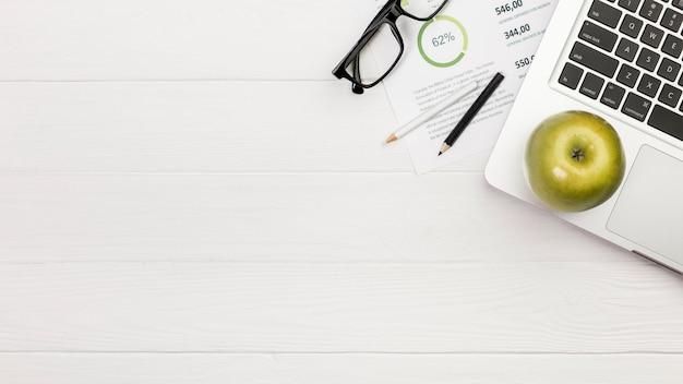 Maçã verde no laptop com lápis de cor e óculos no plano de orçamento sobre a mesa