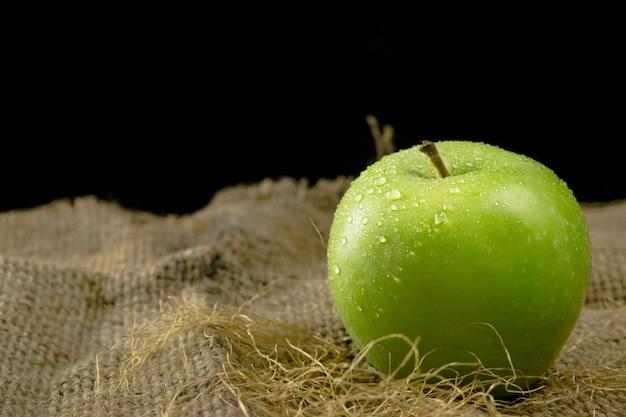 Maçã verde no saco de gunny contra o fundo preto, único fruto molhado da maçã.