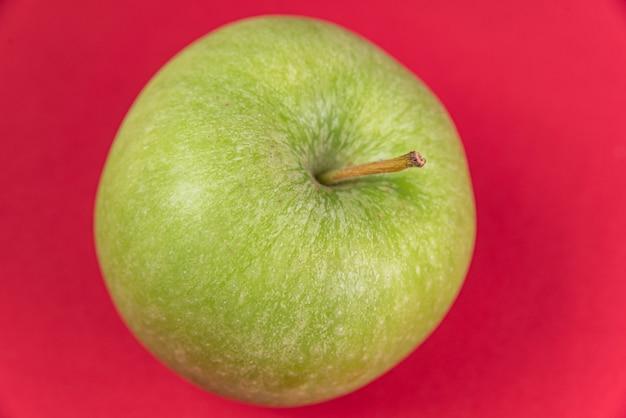 Maçã verde sobre fundo vermelho
