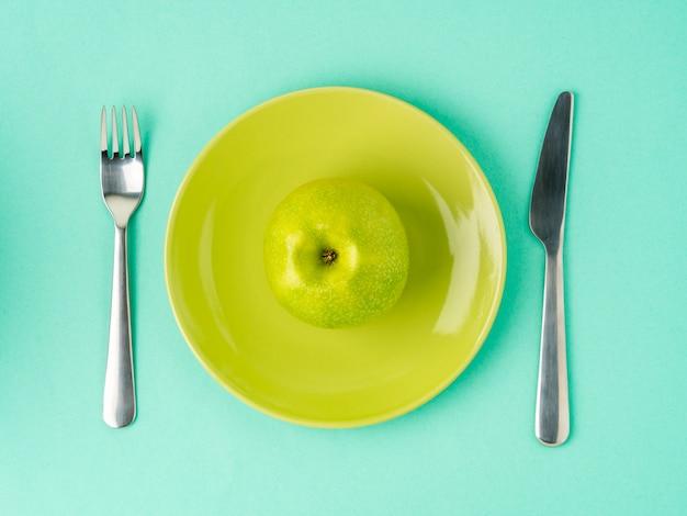 Maçã verde suculenta crua madura em uma placa amarela, forquilha, faca. dieta como estilo de vida.