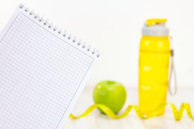 Maçã verde, uma fita métrica, caderno e uma garrafa de água para escrever sobre uma superfície de madeira clara. preparação para a temporada de verão e praia, perda de peso e conceito esportivo