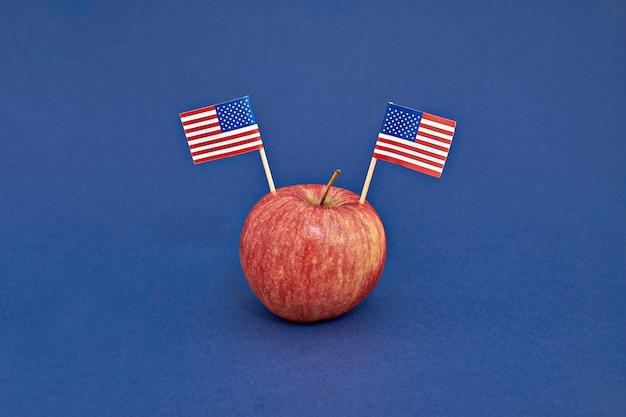 Maçã vermelha com duas bandeiras dos eua sobre fundo azul. dia de presidentes do conceito de américa
