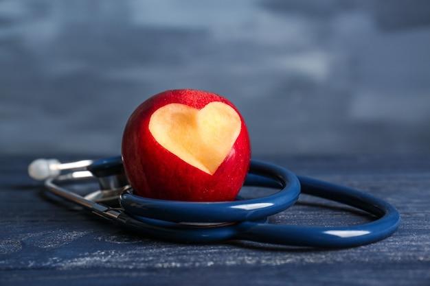 Maçã vermelha com recorte em forma de coração e estetoscópio na cor de fundo