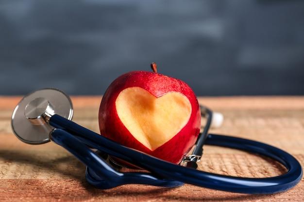 Maçã vermelha com recorte em forma de coração e estetoscópio na mesa de madeira