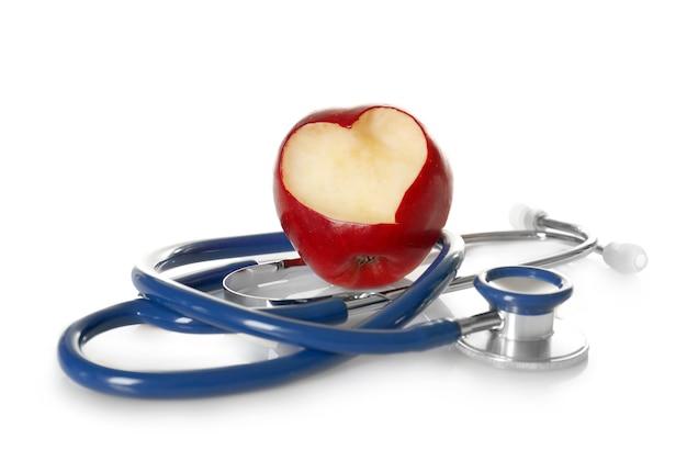 Maçã vermelha com recorte em forma de coração e estetoscópio sobre fundo branco