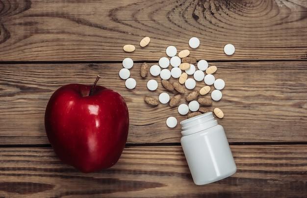 Maçã vermelha com um frasco de comprimidos em uma mesa de madeira