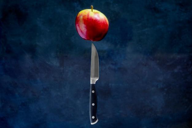 Maçã vermelha e faca de frutas voando no ar em fundo escuro. conceito de levitação de alimentos.