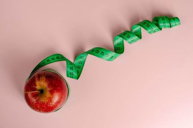 Maçã vermelha e fita métrica verde em rosa