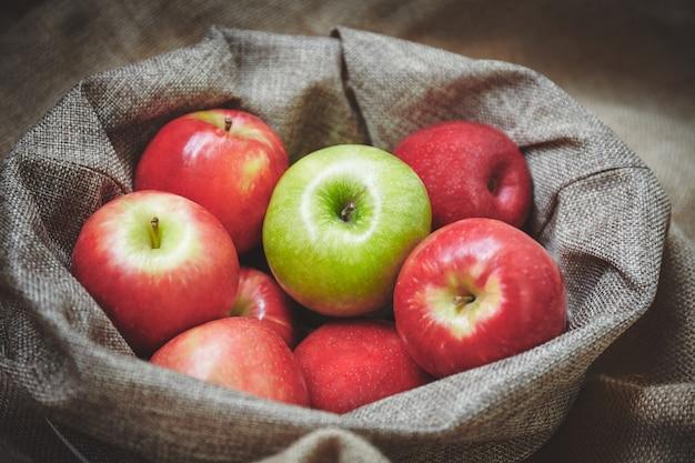Maçã vermelha e maçã verde no cesto com textura de fundo de pano de saco