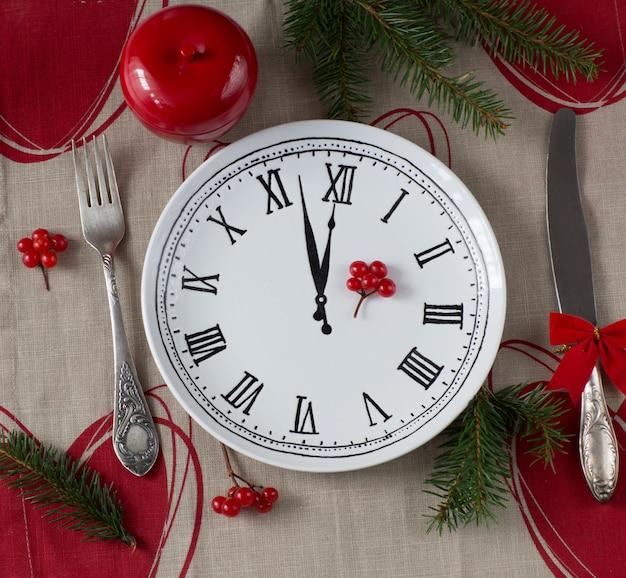 Maçã vermelha em cima da mesa, ramos de abeto, talheres e um prato com uma foto de um relógio