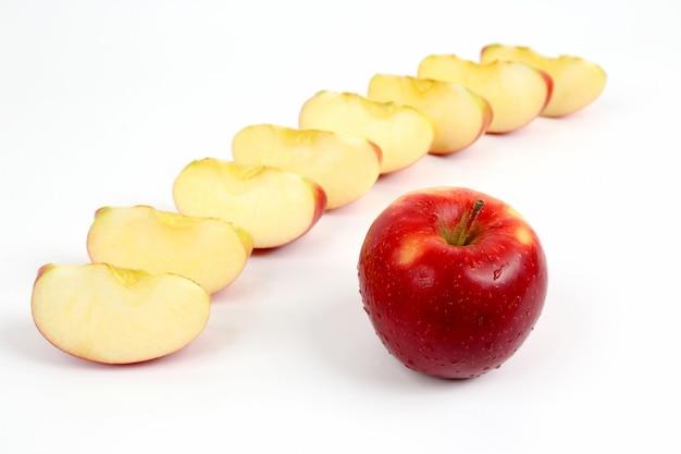 Maçã vermelha em um fundo de pedaços de maçã cortados