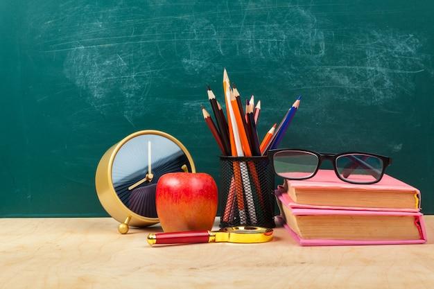 Maçã vermelha em uma pilha de livros, papel e lápis em cima da mesa